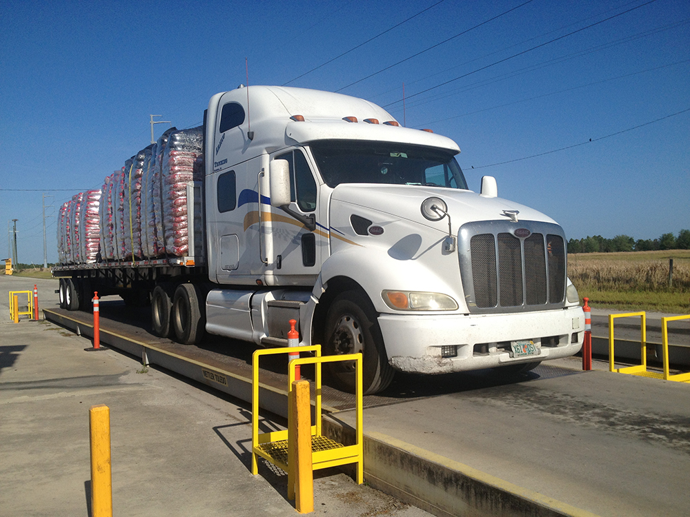 large white semi truck with cargo at weigh station
